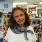 Carolyn Clasen models a cool triangle scarf she crocheted using Claudia Hand painted Sport Wt.  It's double crochet - and you start in the center to create a triangle pattern.. Easy, says Carolyn!