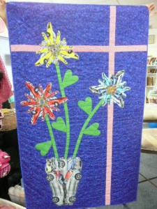 "Cynthia Griffin calls this creative quilt ""Say it With Flowers"". As the next photo shows, these flowers are made of cars...."