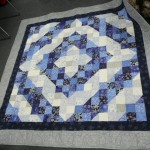 "This Scrappy Split 9 Patch was Lynette Johnson's 2012 Christmas Quilt.  It was fun and fast - and her first quilt on her new longarm!  She calls it ""Silver Snowflake""."